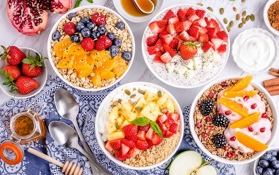 bowls of oatmeal and yogurt with fruit on a table