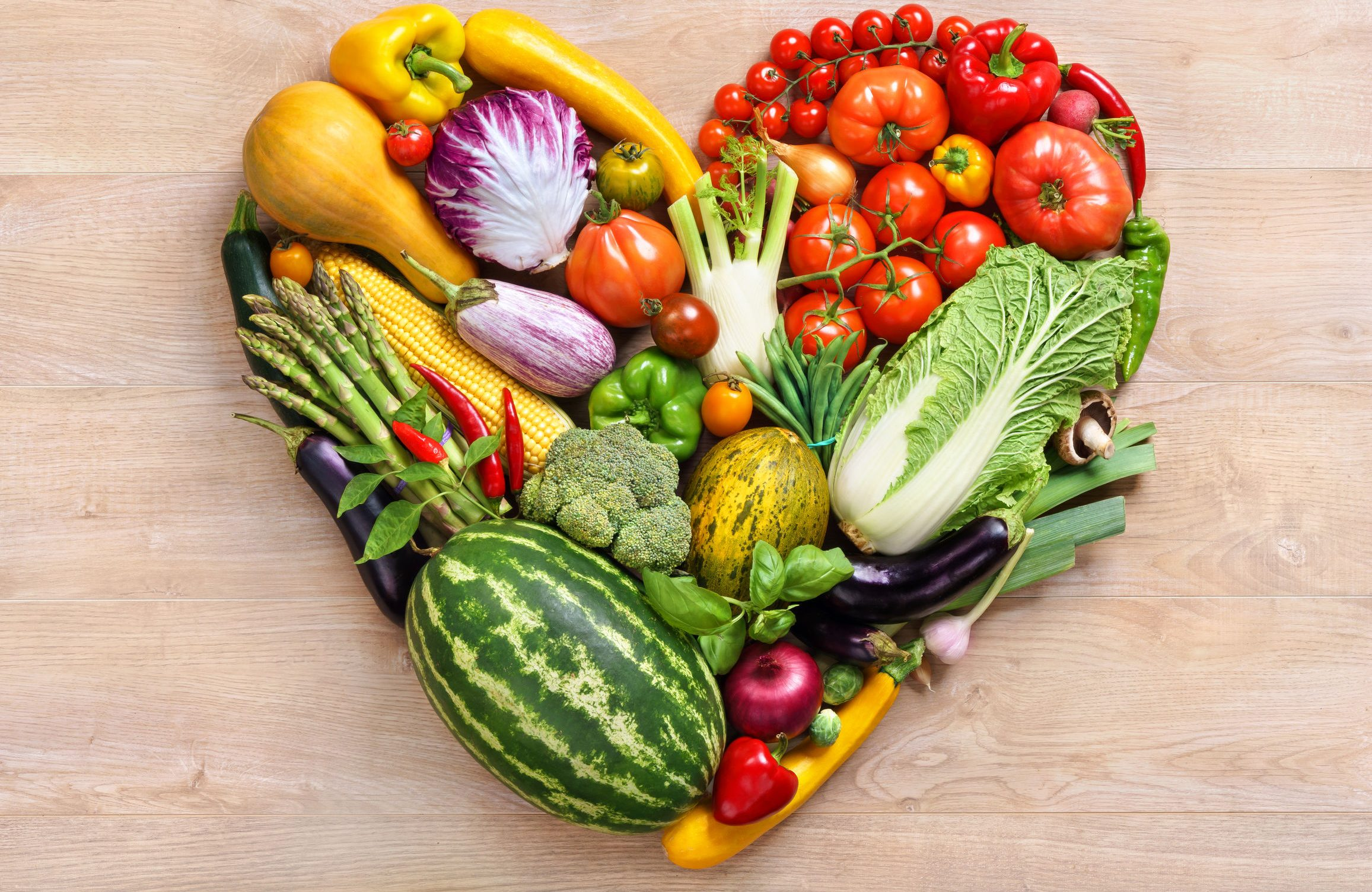 Healthy fruits and vegetables making up the shape of a heart
