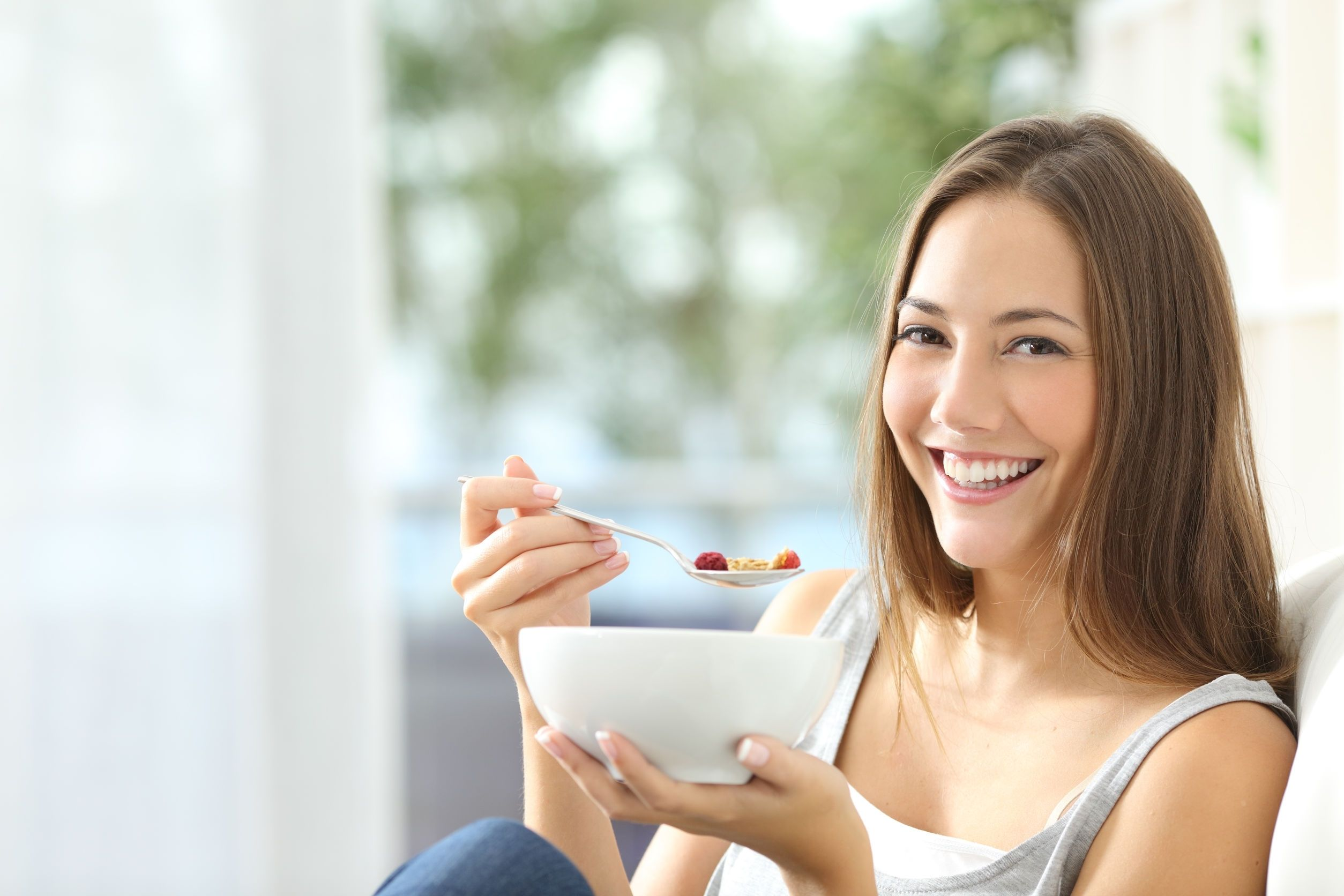Woman happy to eat a healthy bowl of fruit and cereal.