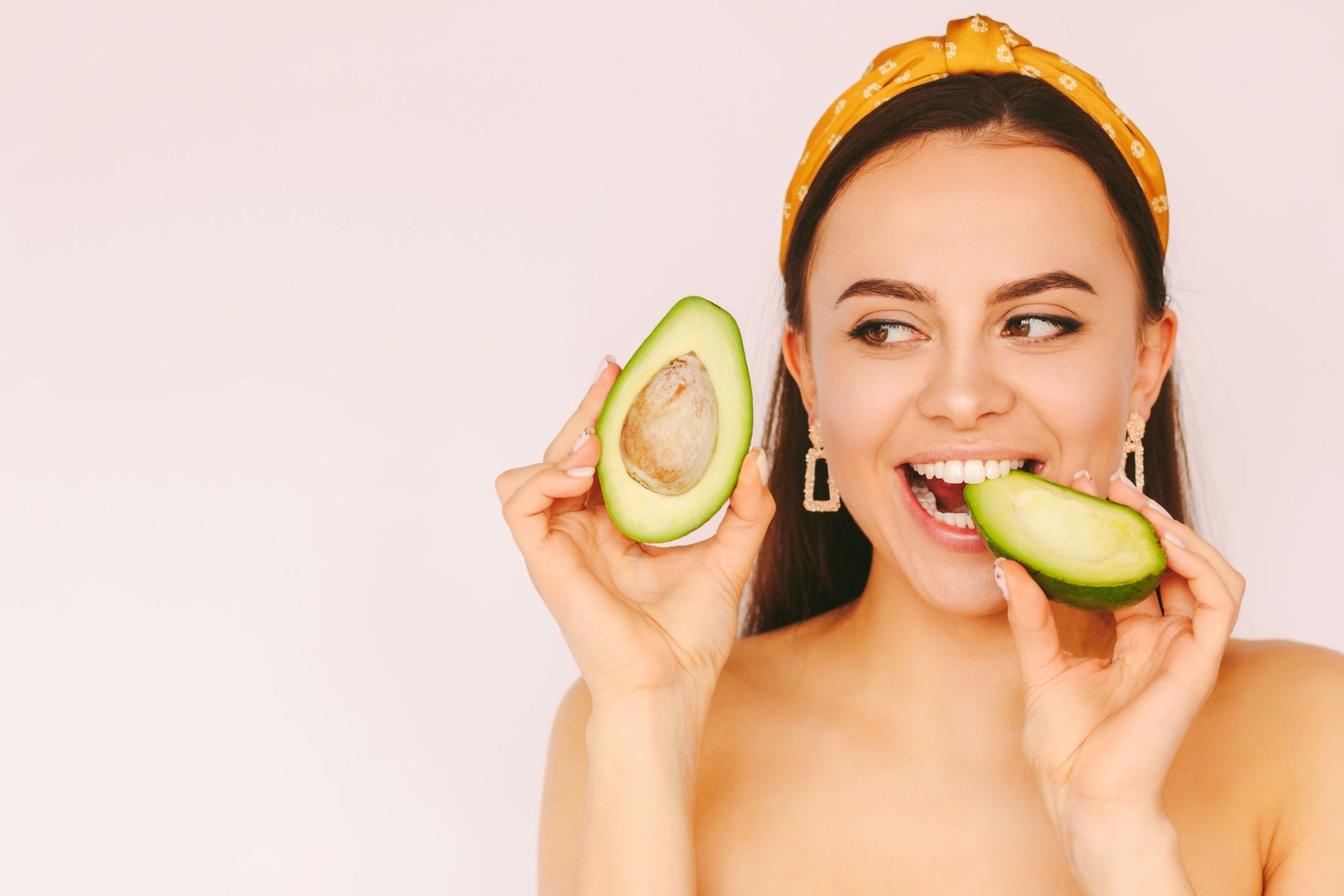 Woman eating avocado because it is part of her healthy skin diet.