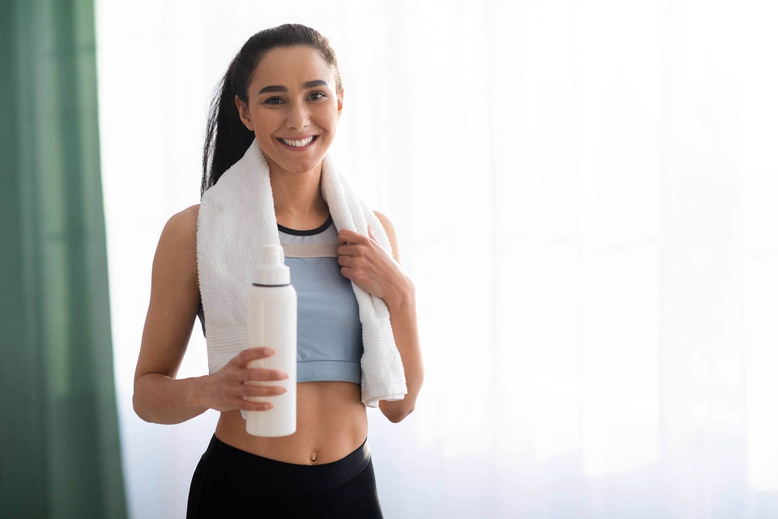 woman using towel on shoulders and holding water bottle after finishing workout routine