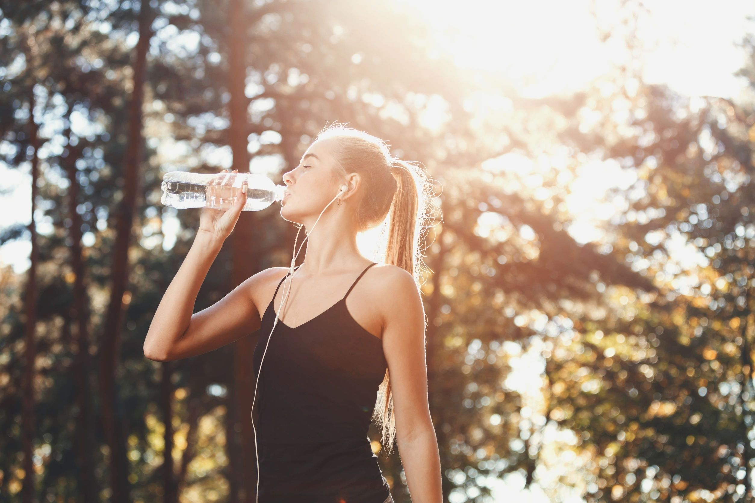Woman drinking water and listening to music after working out to increase her stamina
