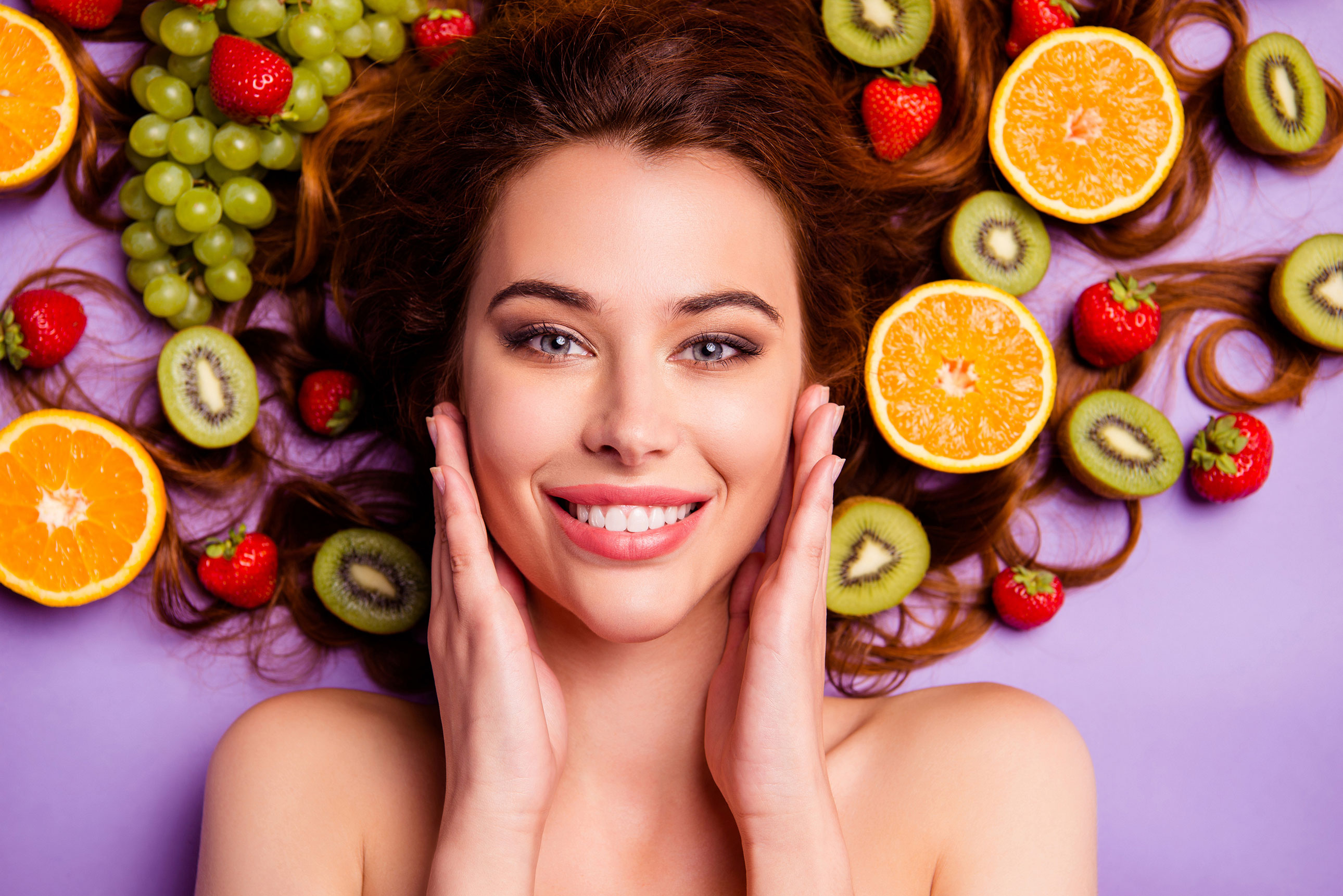 Woman eating healthy fruits and vegetables as part of her healthy skin diet.