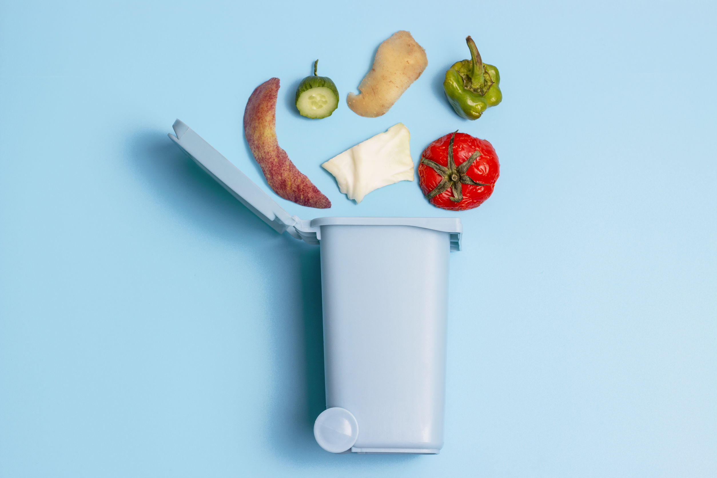 Food waste and trash can on blue background, concept of garbage sorting