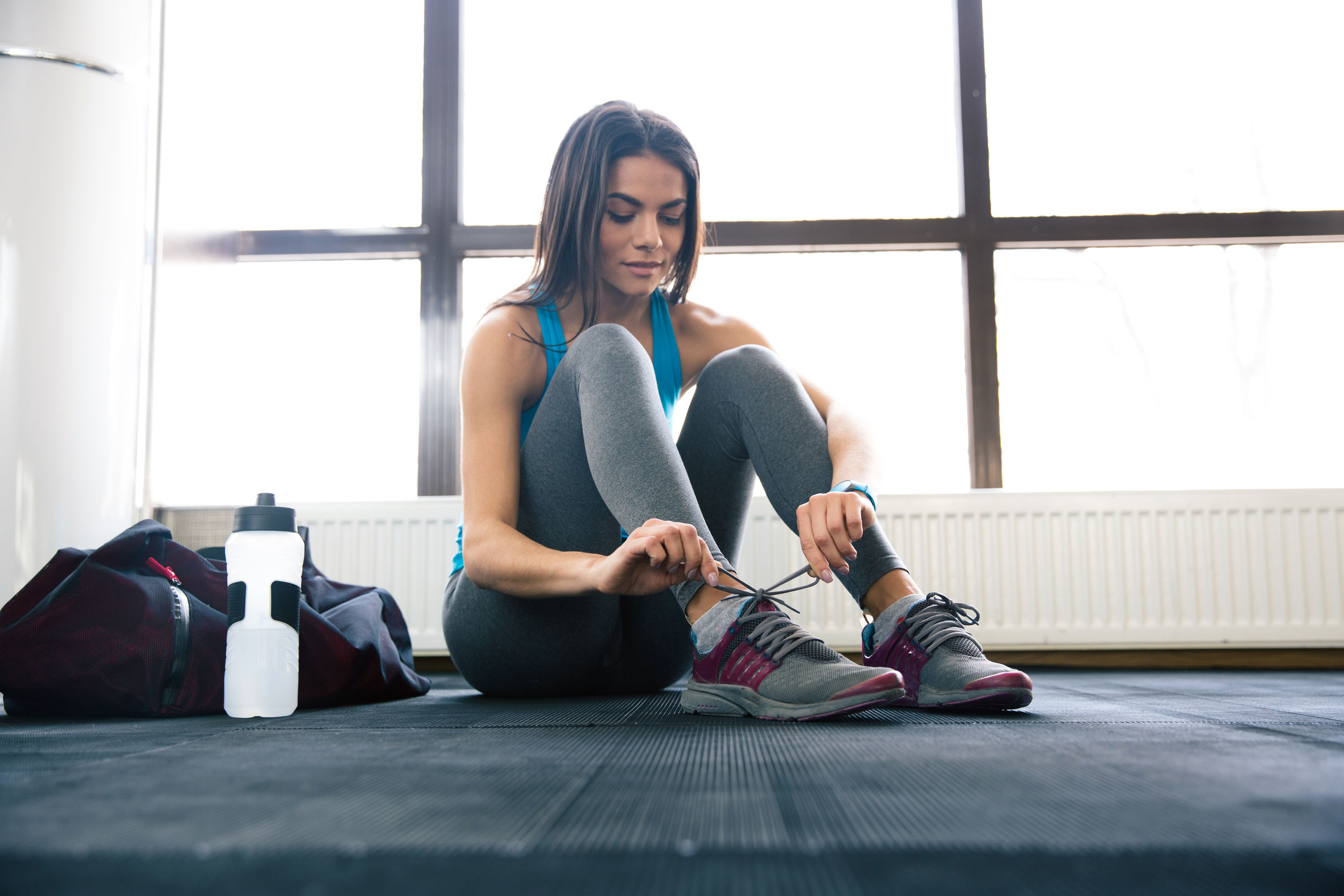 woman tying shoelaces at gym to get ready to workout