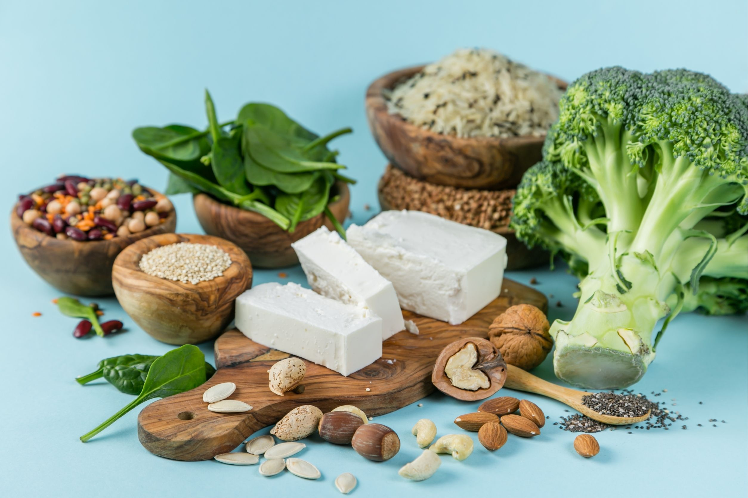 Vegetarian diet foods like broccoli, tofu, nuts, spinach, and rice