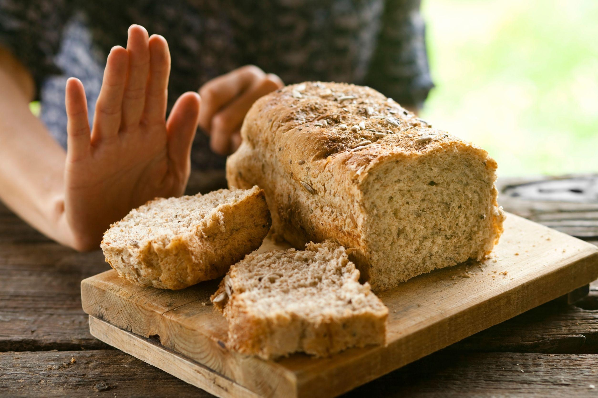 woman who is gluten intolerant rejecting bread